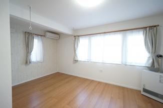 13帖の広々とした洋室。ホワイトの壁に木のぬくもりを感じるフローリングがよく映えます。写真から見て右側はすべて収納スペース。