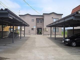 屋根付き車庫があり、落ち着いたグレーの外観のアパート