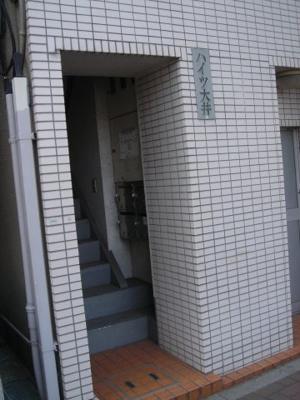 白いタイル張りのマンションです。1階の入り口横にはコインランドリーがあります。