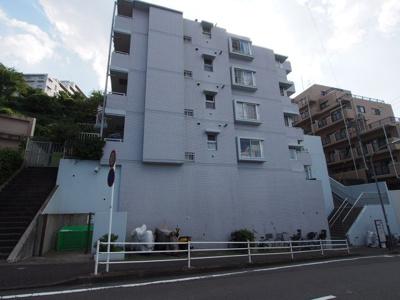 外壁は白いタイル張り、7階建てのマンションです。