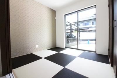 和室はお洒落なモノトーンの琉球畳でリビングからだけでなく、廊下側にも扉があります。収納もしっかり付いています。掃き出し窓が明るく風通しのよい室内です。