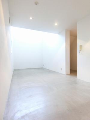 南東向き角部屋二面採光洋室16.8帖のお部屋です♪上部の窓からあたたかな光が入ってきます!床は雰囲気のあるモルタル造☆収納スペースもあります☆