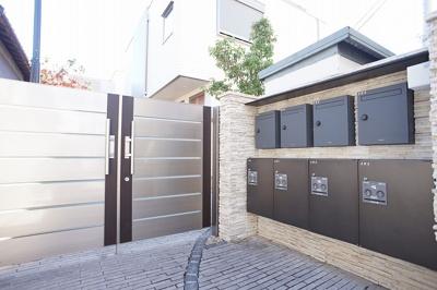 建物に入る直前に現れる門扉とポスト。各世帯専用の宅配ボックスも設置しています。