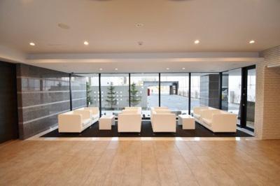 風合いのあるクロスの壁とやさしい間接照明がホテルのような雰囲気を演出するエントランス