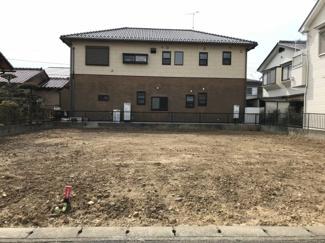 写真の左側の白い建物がある敷地が対象物件です。現在は更地です。
