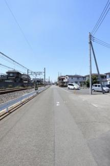 幅員約6mの前面道路の写真です。物件は右側です。左側(南側)は線路なので建物が建つこともなく日当たりは確保されますね。2019年6月14日12:30頃撮影。