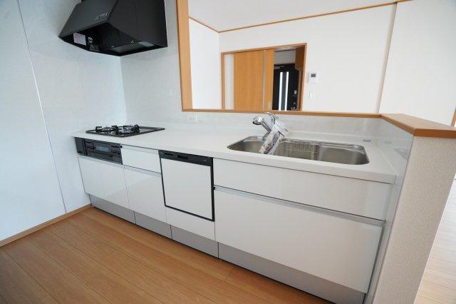 対面システムキッチンは白色でおしゃれですね。3つ口コンロでお料理がたくさんできますよ。広いシンクも使いやすそうですね。家族一緒にお料理できますよ。