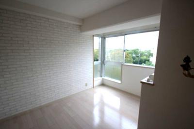 別角度からみた洋室(6.7帖)です。 ホワイトのレンガ調のクロスがオシャレなお部屋ですね♪ 植木のグリーンが映えキレイですよね♪