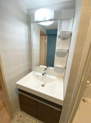 鏡が大きくてシンプルな洗面台を新設。背面のブルーの壁紙が鏡に映ってキレイです