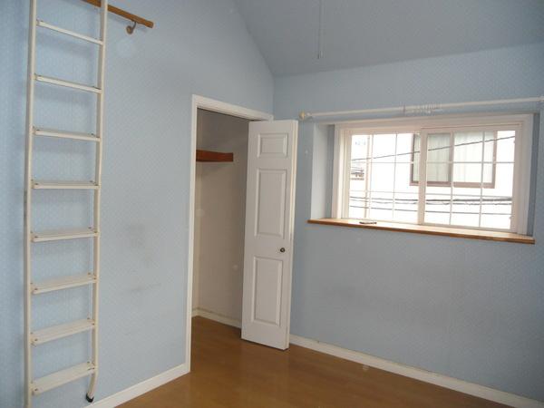 2階洋室6帖。壁が優しいブルーが特徴的。収納もあります。