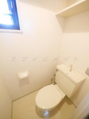 窓のあるトイレ・上部には棚が付いています。