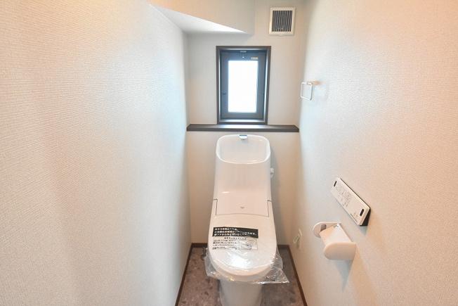 LIXILの壁リモコン付シャワートイレ。フチレスタイプの便器でお掃除もしやすいと評判です。