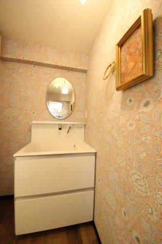 やさしいピンク系の壁紙を選んだ洗面スペースには、シンプルなタイプの洗面台を設置 鏡はインテリアにぴったりくるものを選んでいます