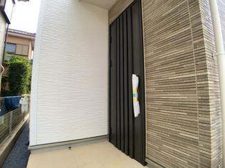 玄関です。1階LDKには目をみはるアクセントクロスと4m超えのTV等のカウンターが設置されています。