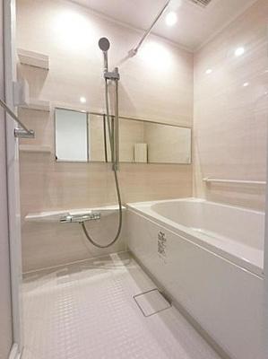 乳白色で清潔な印象の浴室は高齢者にも配慮された手すり付き。