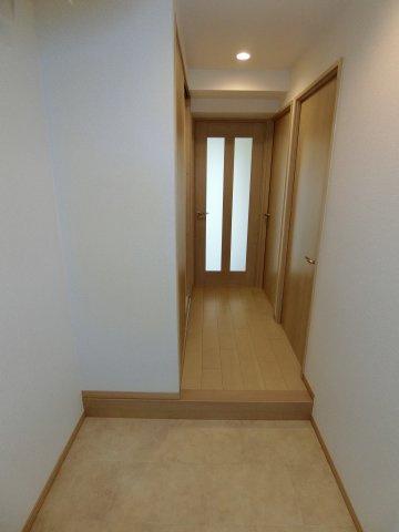 玄関からまっすぐ廊下を進むとリビングがあります。 高層階・角部屋ならではの日当たりで廊下まで光が差してきています。