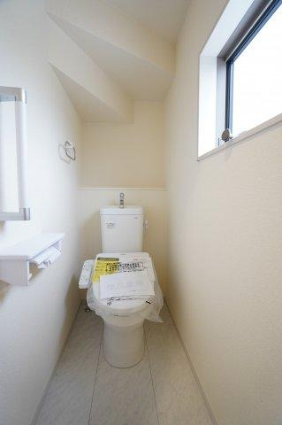 階段下を上手に利用した1階の温水洗浄便座のトイレです。飾り棚にお好きな小物など置けますよ。窓があり明るく、手すりがあり安心ですね。