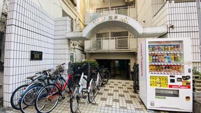 マンション入り口に駐輪場、自動販売機があります。