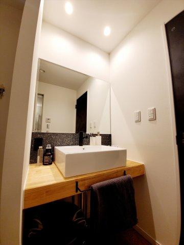 紺色の落ち着いたタイルと大きな鏡がお洒落な洗面台