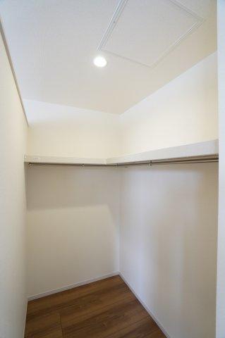 ダウンライトもあり、棚とパイプ付きのウォークインクローゼットです。