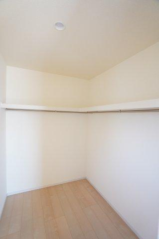 洋室のWICもたっぷり収納できますよ。棚とパイプが設置されていて便利ですね。
