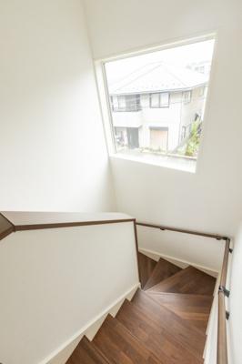 玄関部分は木目調の外壁で、明かり取りの窓付きの玄関ドアです。