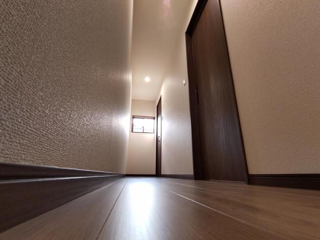 【リフォーム後写真】こちらは一階の廊下になります。トイレ、洗面脱衣所、納戸にアクセスできます。窓を新設したので日中でも明るいです。