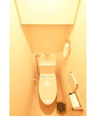 収納棚付きの壁式タッチパネルのウォシュレット一体型トイレ。