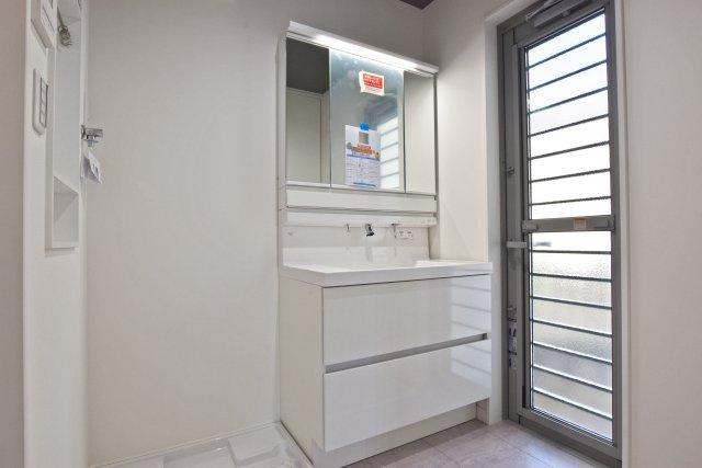 -同社施工例- 3面鏡を使用した防水パン仕様の洗面台。すりガラスの勝手口から光をたくさん取り込みます。