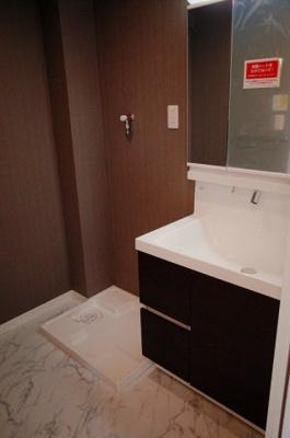 洗面化粧台と洗濯機防水パン。洗面化粧台は三面鏡付きのシステム鏡台です。