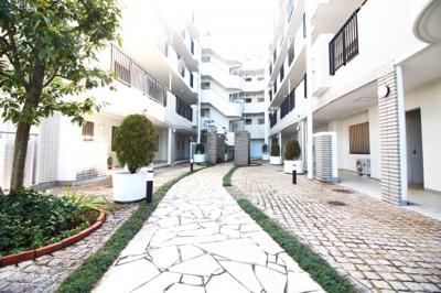 《マンション中庭》植木が並ぶマンションの中庭は、お洒落な石畳のアプローチがマンション入り口まで案内してくれます。