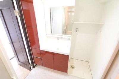 赤のアクセントが目を引く身支度にも便利な洗面化粧台です。