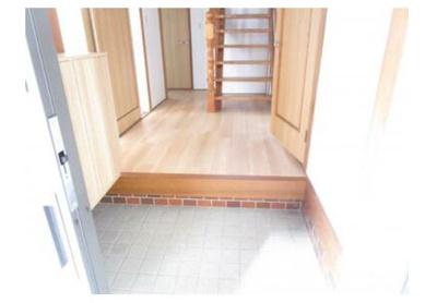 玄関ホール写真。天井と壁は白色基調のクロス張りにしました。廊下の床はフロアタイルを重ね張りにしています。広めの空間になっています。