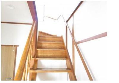 階段写真。天井と壁をクロス張りにし、踏板はクリア塗装でしあげました。また手すりを新設しました。