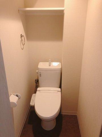 白を基調とした清潔感のあるトイレです。 上段にはトイレットペーパーのストックにも便利な棚がついています。 温水洗浄便座完備です。
