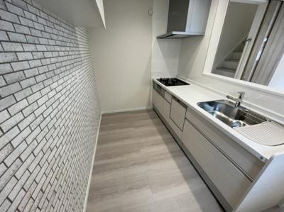 レンガ調のアクセントクロスが素敵なキッチンです。 吊戸棚がなく開放感のある広々とした対面式キッチンです。 食洗機完備で後片づけも楽々ですね♪