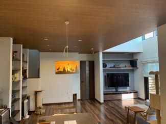 キッチンから見たリビングダイニング。空間造りに必要な高い低い、奥行き感と誘いのバランスを吹き抜けとリビングの天井と全体の色、差し込む光の位置で上手く造り上げております。