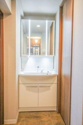 3面鏡の洗面化粧台。鏡の裏側は収納になっております。