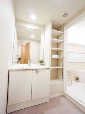 洗面化粧台の横には便利な収納棚があります。