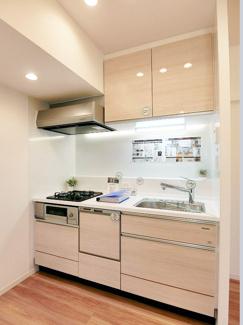照明が明るく照らし出す白を基調としたキッチンは便利な食洗器付