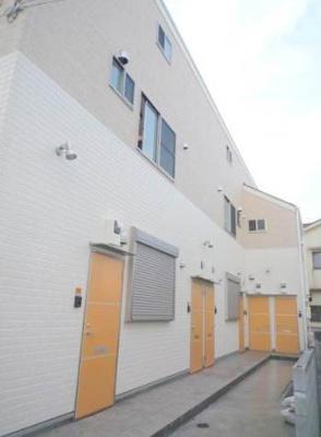 一軒家風な明るい壁面にアパート扉も特色があります