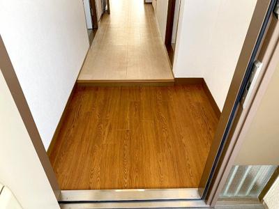 【現地写真】玄関を開けると、明るい日が差し込むリビングへと誘う廊下。