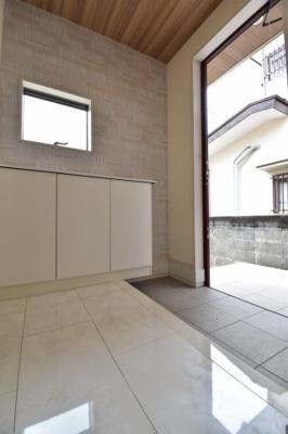 大理石調の光沢あるフローリングが高級感を演出している玄関スペース。大容量のシューズボックスも完備。