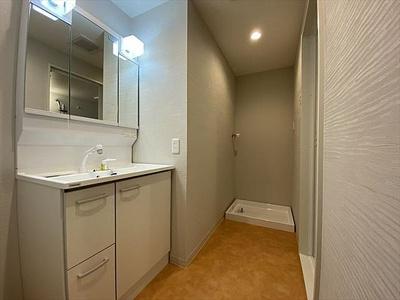 朝の身支度にも便利な洗面化粧台。奥に室内洗濯機置場がございます。