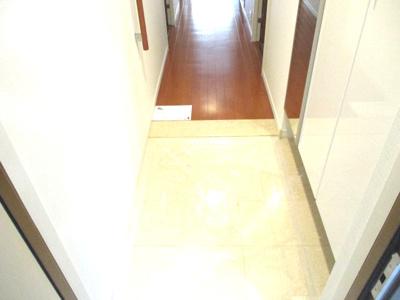大理石調の玄関口。高低差なく室内へ。