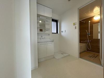 窓のある洗面スペースには防水パン付洗濯機置場付き。