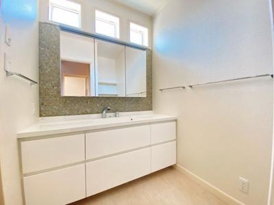 大きな三面鏡の洗面台もこだわりポイント。収納スペースも広く、大人が並んで使っても充分余裕がありますね。