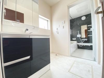 清潔感のある白を基調とした洗面室はシックな色の洗面収納扉で引き締まった印象に。小窓からの採光で明るく、風通しがいいので湿気対策も考慮されています。シンプルな洗面台は収納力だけでなくシンクも広いです。