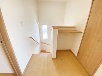 手すり付きでゆるやかなカーブの階段は上り下りも安心ですね。2階ホールに棚スペース設けています。