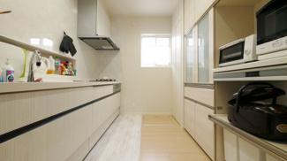 白を基調としたスッキリとしたワイドタイプキッチン。便利な大型スライド収納。